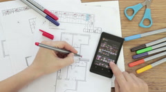 Designer's desk with architectural blueprint and mobile phone, top view HD Stock Footage