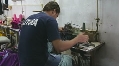 Man preparing to work on a sewing machine in workshop in Mumbai, back view. Stock Footage