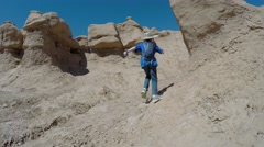 A boy runs through rock formations in goblin valley Stock Footage