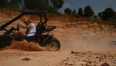 Buggy rushes by, raising clouds of sand close up - stock footage