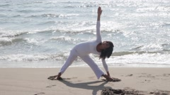 Mature woman practicing Yoga pose on sandy beach Stock Footage