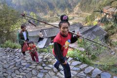 Asian woman carrying a yoke - stock photo