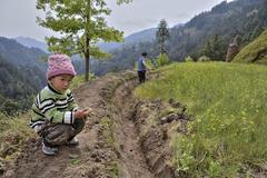 Farmer works soil  in mountainous area, next to boy Stock Photos
