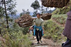 Peasant girl carries weight on yoke, mountainous area rural China. Stock Photos