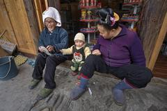 Two Asians and year-old child, on threshold of rural shop. Stock Photos