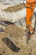 Excavator arm with bucket full of dirt Stock Photos