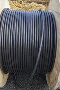 Roll of black industrial cable on large wooden reel Stock Photos