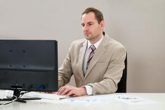 Mid Adult Businessman Working On Computer At Workplace Stock Photos