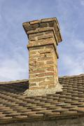 Old brick chimney with old tiles roof - stock photo