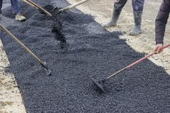 Road construction crew used shovels to scatter more asphalt - stock photo