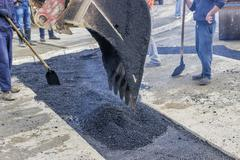 Workers patching asphalt during road repairing works Stock Photos