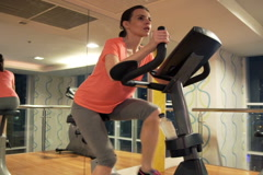 Young woman riding stationary bike in gym at night NTSC - stock footage