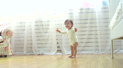 One year a small baby walks funny,dolly shot Stock Footage