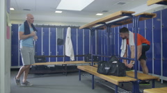4K Happy sports players or gym buddies high five & chat together in locker room Stock Footage