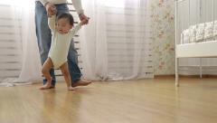 father teaches baby to walk,dolly shot - stock footage