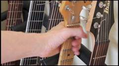 Picking up guitar form guitar rack Stock Footage