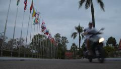 Two motorbikes passing by on the background of international flags Stock Footage