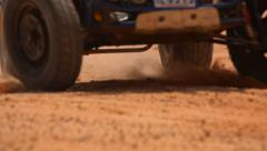 Wheel of the buggy running past in the clouds of sand - stock footage
