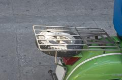 Black spare wheel under grill on green scooter motorcycle Kuvituskuvat