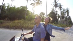 Young Couple Riding Motor Scooter Along Country Road Stock Footage