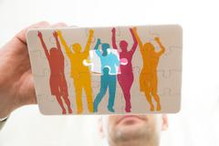 Close-up Of Person Hand Making Colorful Human Figure Of Puzzle - stock photo