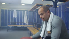 4K Portrait of smiling man holding a football sitting alone in gym locker room Stock Footage
