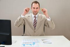 Businessman Inserting Earplug In Ears At Desk In Office - stock photo