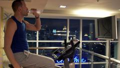 Young handsome man drinking water at riding stationary bike in the gym HD Stock Footage