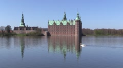 Swan swimming in front of Frederiksborg Castle on a sunny spring day Stock Footage
