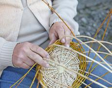 Craftsman hands while creates a wicker basket Stock Photos