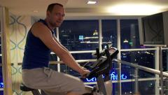 Portrait of young handsome man riding stationary bike in the gym HD Stock Footage