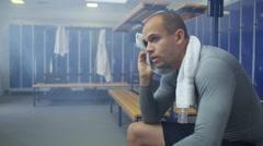 4K Portrait of serious man sitting alone in gym locker room - stock footage