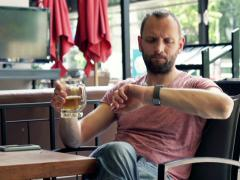 Young impatient man waiting for someone in cafe NTSC - stock footage