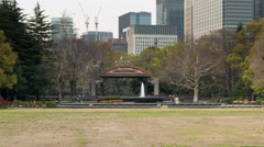 Zoom out time lapse of fountain in Hibiya park at sunset with Tokyo skyline Stock Footage
