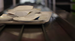 Camera on conveyor belt following an offset tray of dirty dishes - stock footage