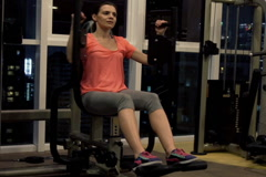 Young woman exercising with body building equipment in the gym NTSC Stock Footage