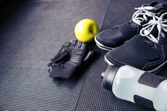 Sports gloves, sneakers, bottle with water and green apple - stock photo