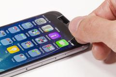 Applying screen protector on mobile phone Stock Photos