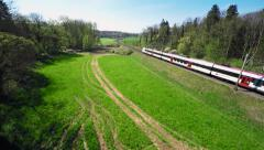 Scenic aerial shot of a commuter train passing through the countryside - stock footage