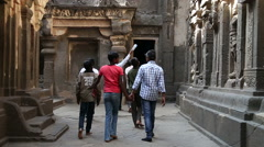 Stock Video Footage of Tourists passing through the rooms of Aurangabad caves.