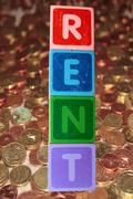 Rent and coins in toy blocks Stock Photos