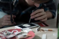 Drug addicted man taking cocaine Stock Photos