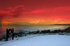 golf tee sign with winter orange sunset sky - stock photo