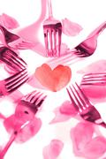 Pink forks surrounding heart shape and rose petals Stock Photos
