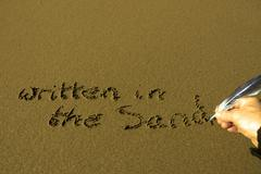 hand written in the sand with feather quill - stock photo