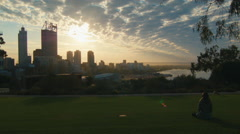 Woman Sitting On The Grass Watching The Sunrise Over Perth City CBD Stock Footage