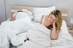 Unhappy Woman With Blanket On Bed While Man Sleeping In Bedroom Stock Photos
