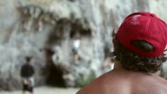Man with a red cap is watching on climbers on the rock wall. Thailand Stock Footage