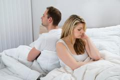 Unhappy Couple With Blanket Sitting On Bed - stock photo