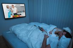 Couple Lying In Bed With Blanket Watching Television Stock Photos